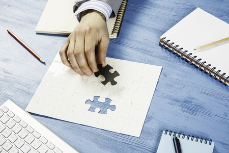 Hand of businessman completing puzzle with missing piece