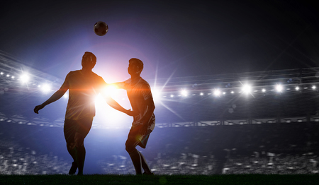 Soccer players at sport stadium fighting for ball . Mixed media Stock Photo