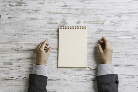 Top view of businesswoman sitting at wooden table and notepad in hands