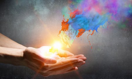 Close up of hand holding splashes of colorful paint 스톡 콘텐츠