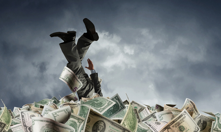 Rich businessman in pile of money banknotes