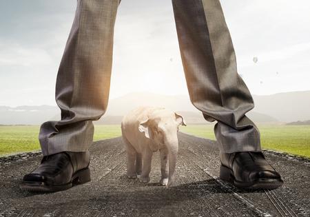 Feet of giant businessman on asphalt road as power concept. Mixed media