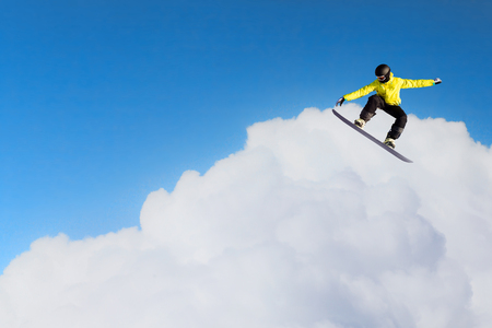 Snowboarder jumping against blue cloudy sky. Mixed media