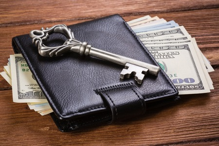 Old vintage key on wallet with money on wooden table
