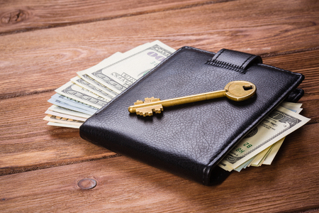 Golden key on wallet with money on wooden table Stock fotó