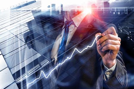 Vista vicina dell'uomo d'affari che attinge i infographs del mercato dello schermo