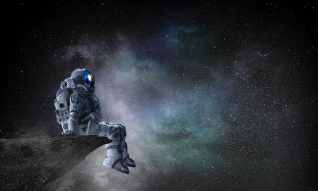 Astronauta seduto sul bordo della scogliera contro il cielo stellato scuro. Tecnica mista