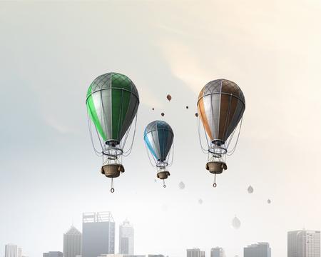 Many aerostats with anchor floating in day sky. Mixed media