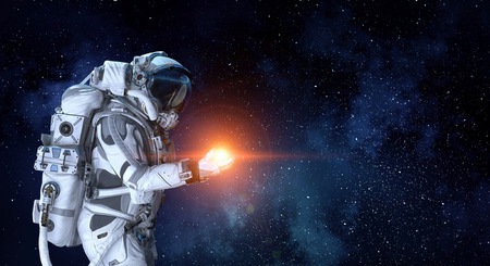 Astronaut and light spot in his palm. Mixed media Reklamní fotografie