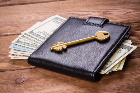 Golden key on wallet with money on wooden table Stock Photo - 102153683