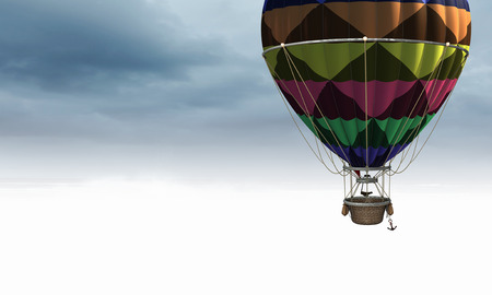Color aerostat floating in day sky. Mixed media