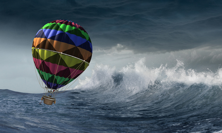 Colored aerostat flying above stromy sea. Mixed media Archivio Fotografico - 103069283
