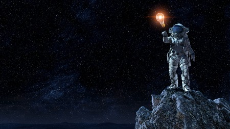 Astronaut pointing with finger at glass light bulb. Mixed media Reklamní fotografie