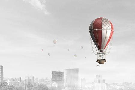 Aerostat floating in day sky above cityscape. Mixed media