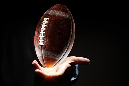 Female hand on dark background and rugby ball in palm Stock Photo