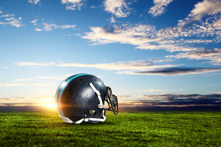 Rugby helmet on green grass and blue sky background. Mixed media Stock Photo