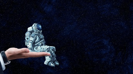 Astronaut sitting in palm against dark starry sky. Mixed media Stock Photo