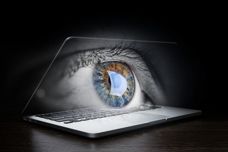 Opened laptop and human eye on screen against dark background