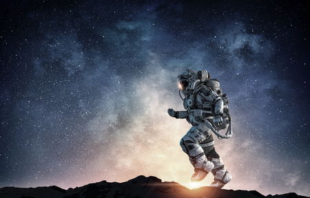 Astronaut in space suit running on planet surface. Mixed media Stock Photo