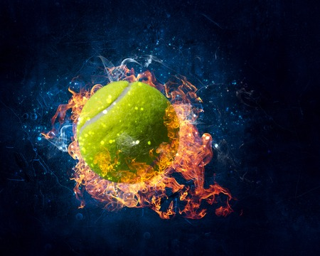 Big tennis ball in fire flames on dark background. Mixed media