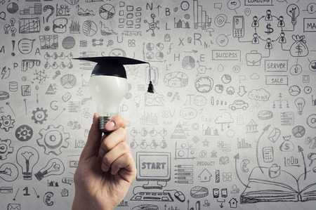 Hand of businessman holding glowing light bulb with graduation hat on it
