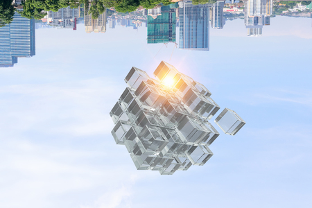 High tech cube figure in sky on cityscape background. Mixed media