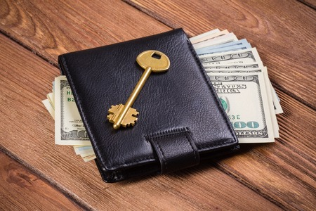 Golden key on wallet with money on wooden table Stock Photo