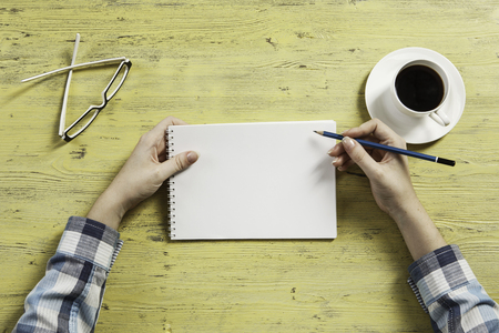 Top view of woman in checked shirt at workplace and blank notepad at table Stock Photo