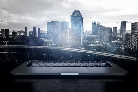 Laptop device and modern cityscape on screen. Mixed media