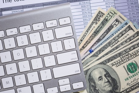White computer keyboard and dollar banknotes as e-commerce concept Stock Photo
