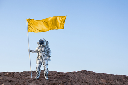 Astronaut man with flag in hand. Mixed media 스톡 콘텐츠