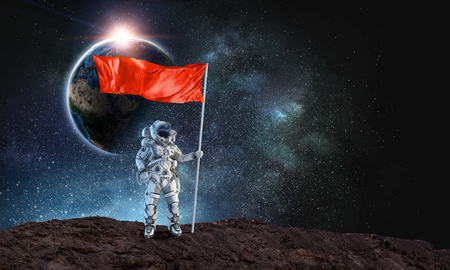 Astronaut man with flag in hand.