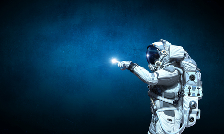 Astronaut pointing with finger at light spot. Mixed media