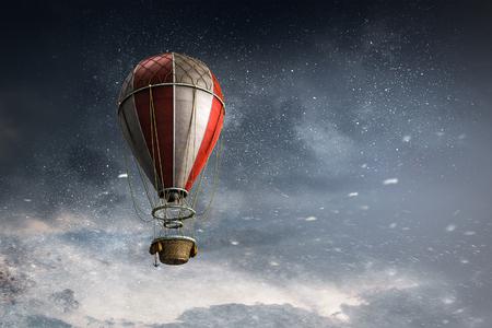Color aerostat floating in dark sky. Mixed media