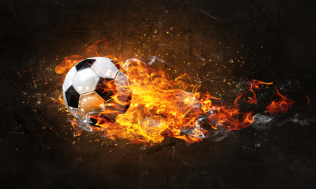 Concept of soccer game with ball in fire flames. Mixed media Stock Photo