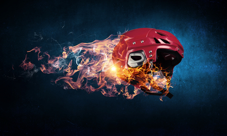 Sport helmet in fire flames on dark background