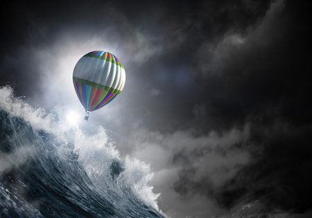 Colored aerostat flying above stromy sea. Mixed media Archivio Fotografico - 103852527