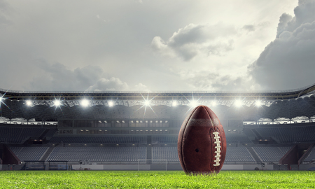 American rugby ball on grass in stadium. Mixed media
