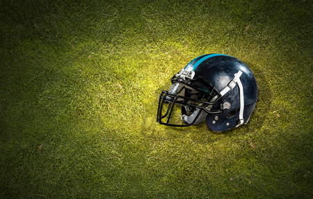 Rugby game helmet on green grass background