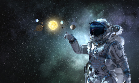 Astronaut pointing with finger at planets of sun system. Mixed media Reklamní fotografie