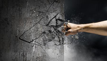 Hand breaking through the wall. Mixed media 版權商用圖片