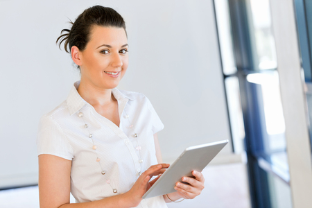 Picture of smiling woman with tablet pc in office
