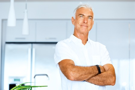 Portrait of a smart senior man with standing in kitchen