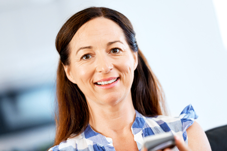 Portrait of pretty woman holding mobile phone