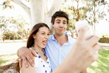 Young couple in the park making their selfi with mobile phone Stock Photo