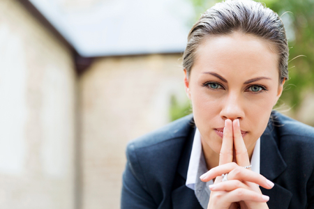 Portrait of young business woman outdoors sitting and thinking Stock Photo