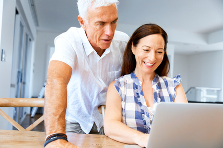 Happy modern couple surfing the net and working on laptop at home Stock Photo