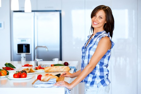 Beautiful woman standing in the kitchen and smiling Фото со стока - 114262275