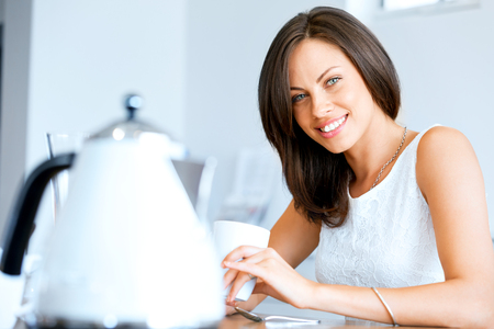 Happy young woman with cup of tea or coffee at home Stock Photo