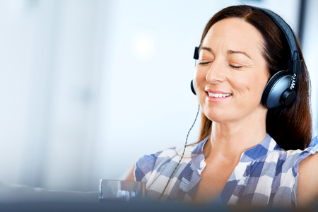 Happy smiling woman relaxing and listening to music